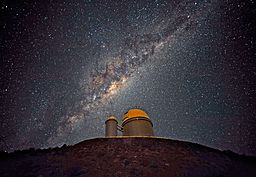 The ESO telescope located at La Silla, Chile. The building has a gold dome, and is sitting on a hill. In the background is the milky way.