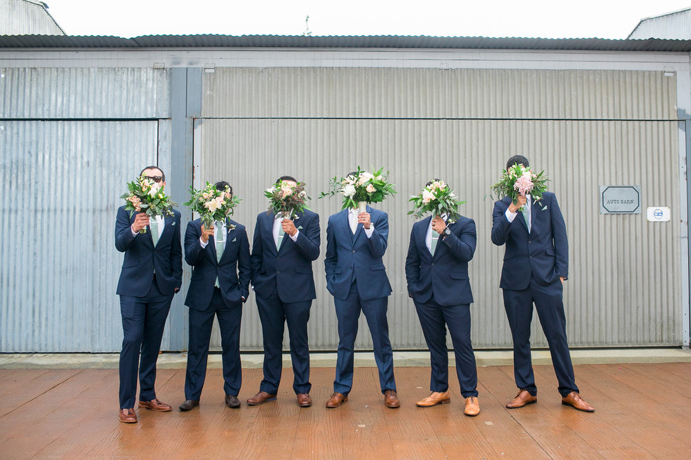 b9453-elegant-country-charm-ranch-wedding-groomsmen-being-silly-with-bridal-bouquets.jpg