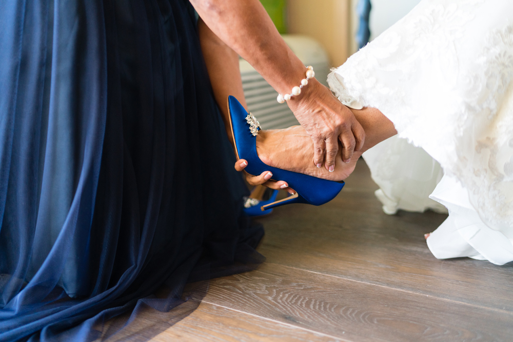 644c7-lively-navy-yellow-harbor-wedding-mom-helping-bride-put-on-shoes.jpg