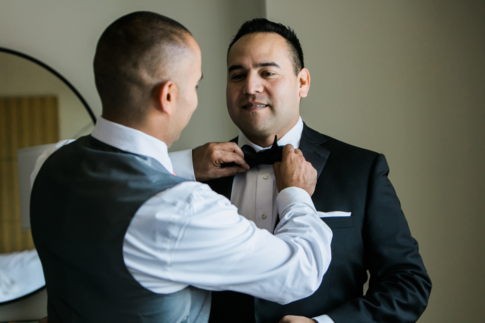6d2a8-pretty-in-pink-vintage-hollywood-fiesta-wedding-groomsman-helping-groom.jpg