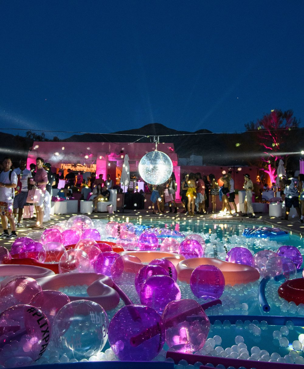 Ultimate Hollywood Coachella Poolside Party disco ball spins above the pool rays shine behind.jpg