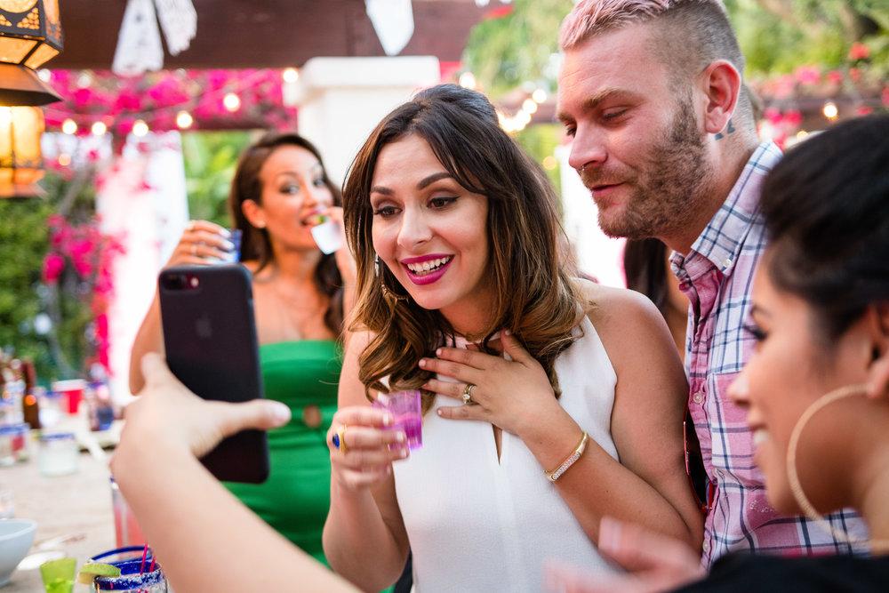 Vibrant Fiesta Backyard Wedding Reception bride checking out picks on cell phone.jpg