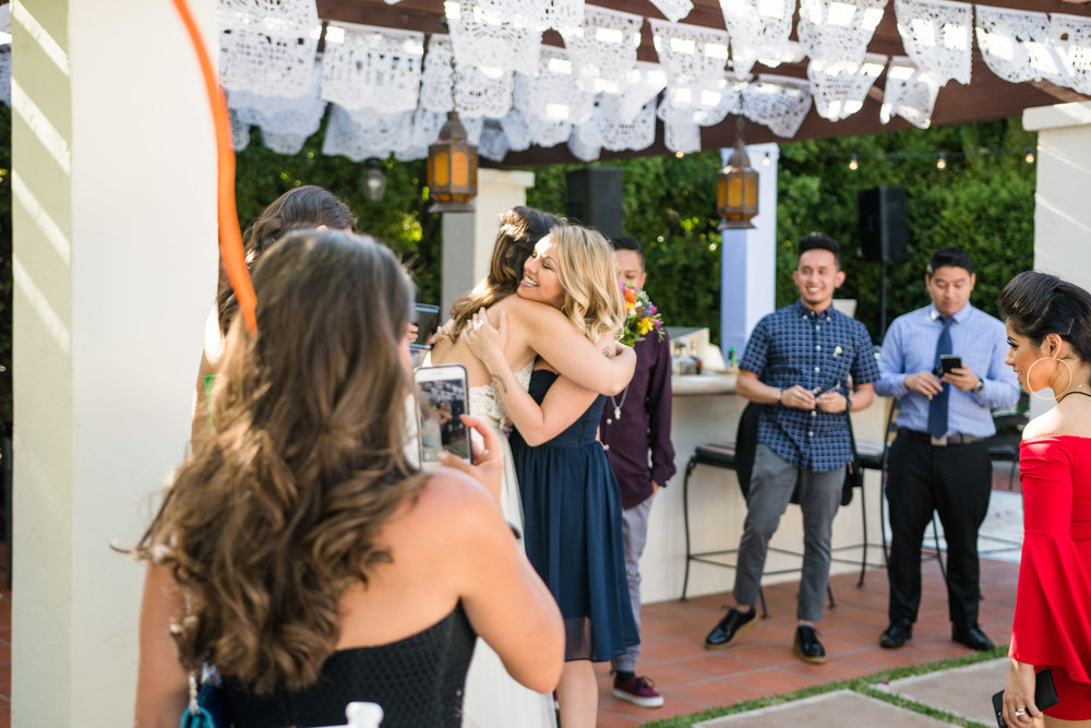 Vibrant Fiesta Backyard Wedding Reception bride hugging happy guest.jpg
