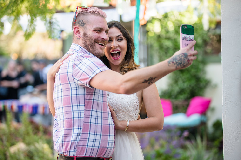 Vibrant Fiesta Backyard Wedding Reception bride posing with another happy guest.jpg