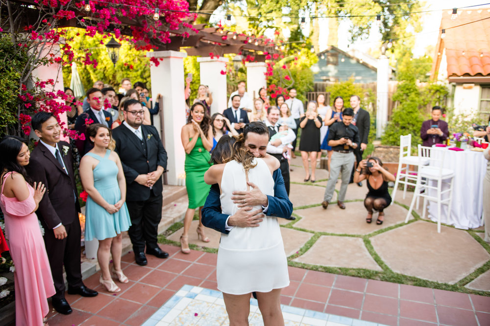 Vibrant Fiesta Backyard Wedding Reception bride hugs groom during first dance.jpg