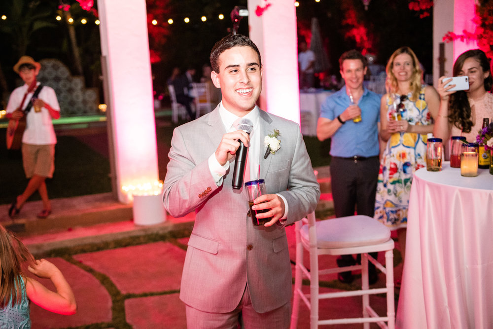 Vibrant Fiesta Backyard Wedding Reception groomsman making a toast.jpg