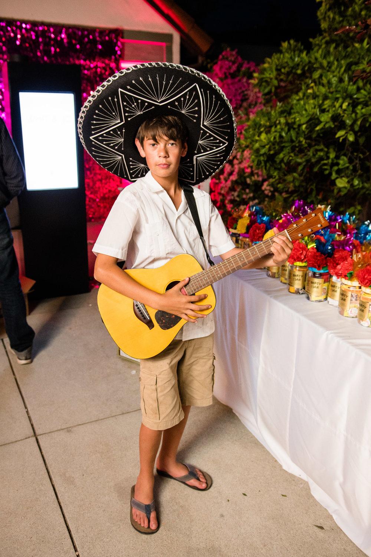 Vibrant Fiesta Backyard Wedding Reception young guest with guitar.jpg