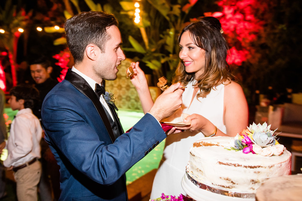 Vibrant Fiesta Backyard Wedding Reception bride and groom feeding eachother cake.jpg