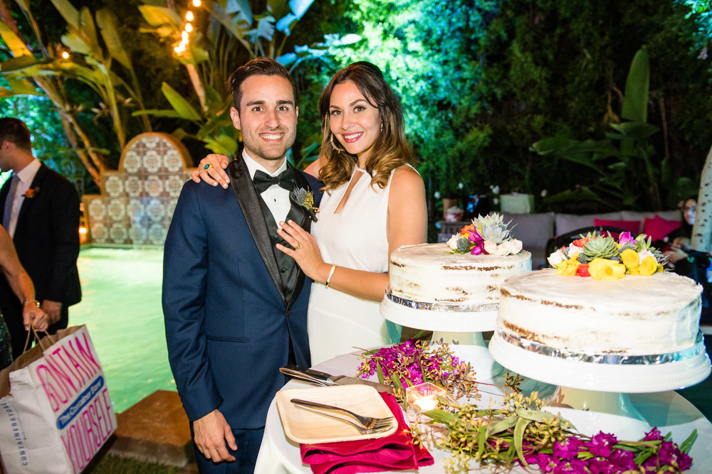 Vibrant Fiesta Backyard Wedding Reception bride and groom with cake.jpg