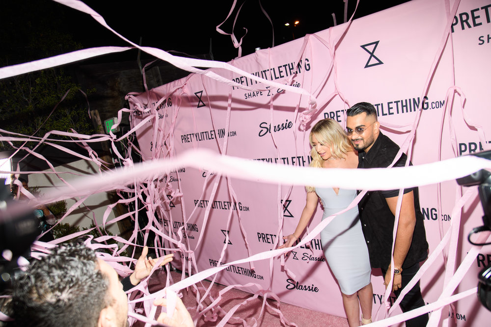 PrettyLittleThing New PLT Shape Collection with Stassie Celebrity Launch Party Stassiebaby and Umar Kamani with pink streamers all around them.jpg