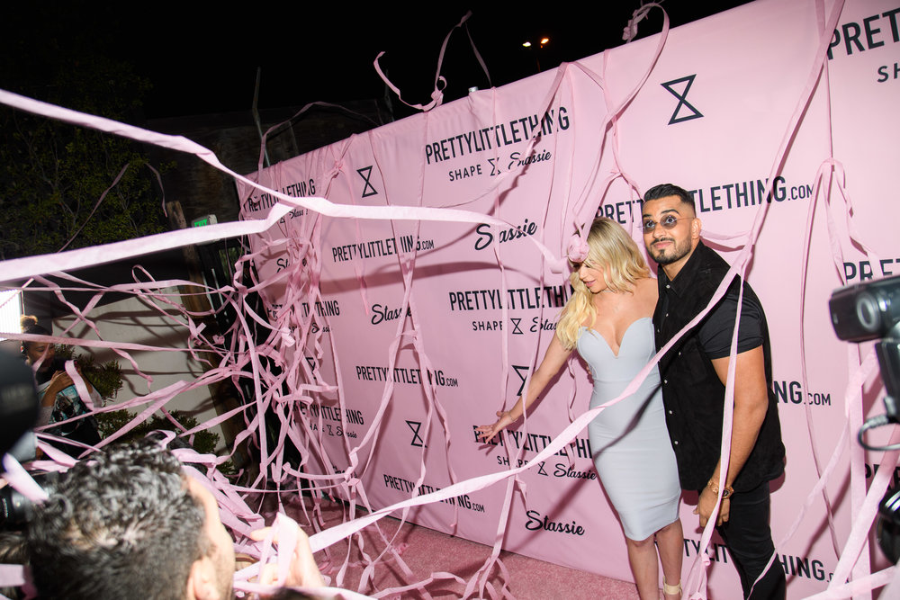 PrettyLittleThing New PLT Shape Collection with Stassie Celebrity Launch Party Stassiebaby and Umar Kamani with pink streamers coming down.jpg