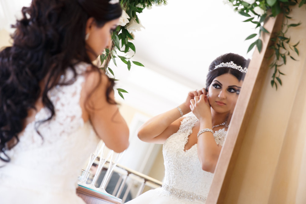 Elegant Pasadena Wedding to Make You Swoon bride adding final jewelry touches.jpg