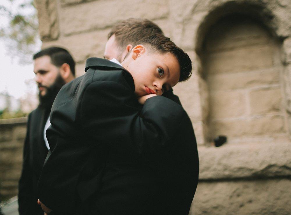 Breathtaking Contemporary Jewel Toned Fall Posh Wedding son hugs his dad.jpg
