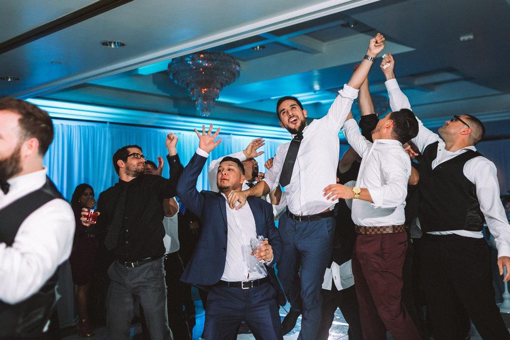 Breathtaking Contemporary Jewel Toned Fall Posh Wedding guys reach for garter.jpg