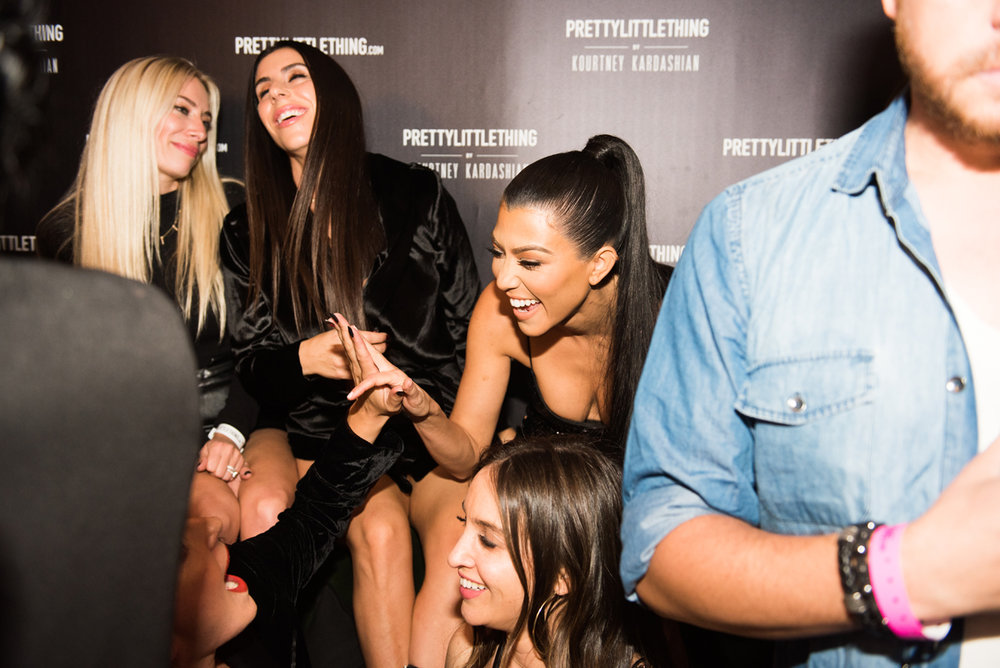 PrettyLittleThing PLT X Kourtney Kardashian Collection Celebrity Launch Party Kourtney laughs with friends.jpg