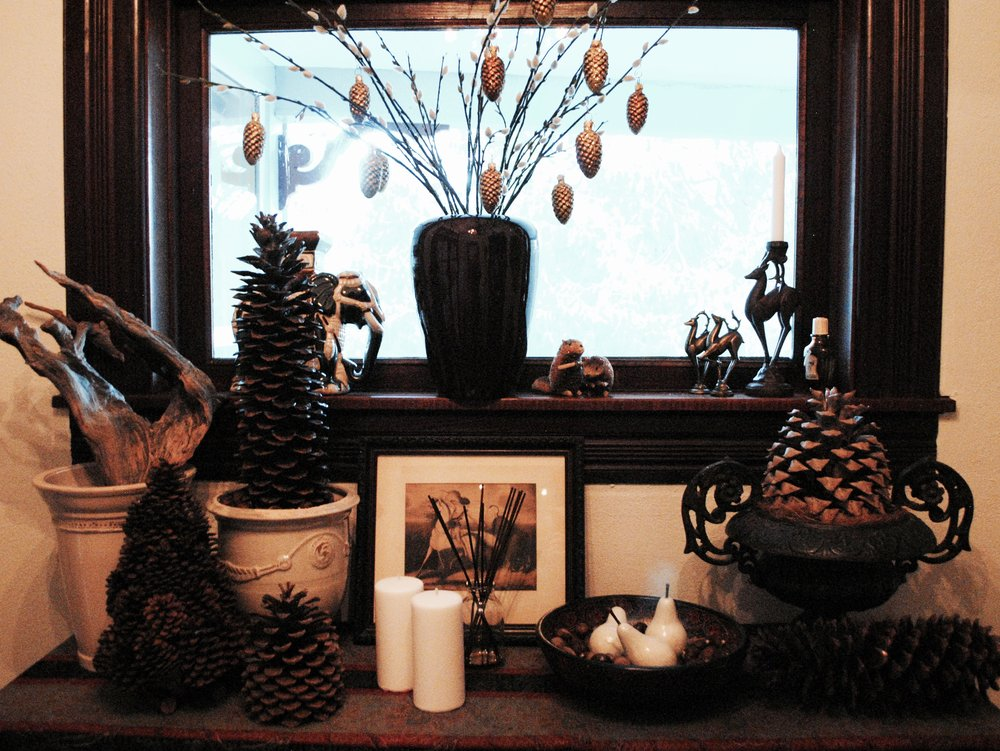 In the vestibule, pine cones, wooden pears, and a bowl of chestnuts on the old Italian ironwood console.