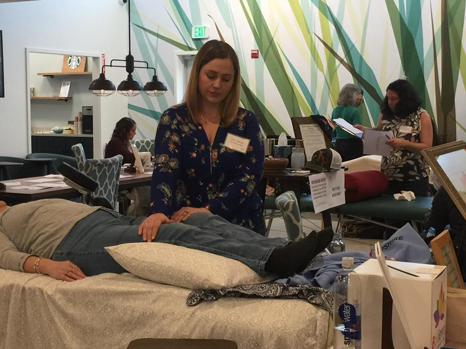 Erin offering treatment to attendees of a True You Wellness event.