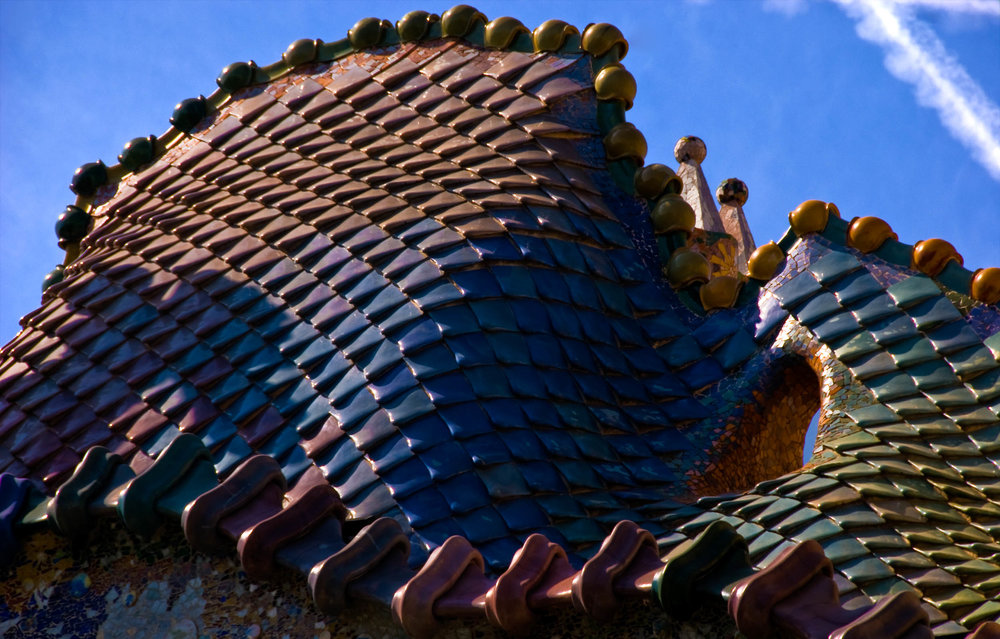 This photograph was taken in Barcelona and shows the details of Antoni Gaudi's Casa Batllo. Casa Batllo is built in the Catalan Art Nouveau style, but is distinctly Gaudi's Modernisme. The roof of the house evokes the scales on the back of a dragon.