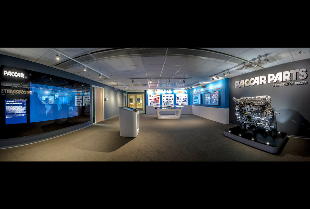 PACCAR Experience - this custom exhibit leverages dynamic 3D projection mapping, custom programming on large all-in-one monitors and a 1:200 scale laser-cut acrylic model of the entire facility.