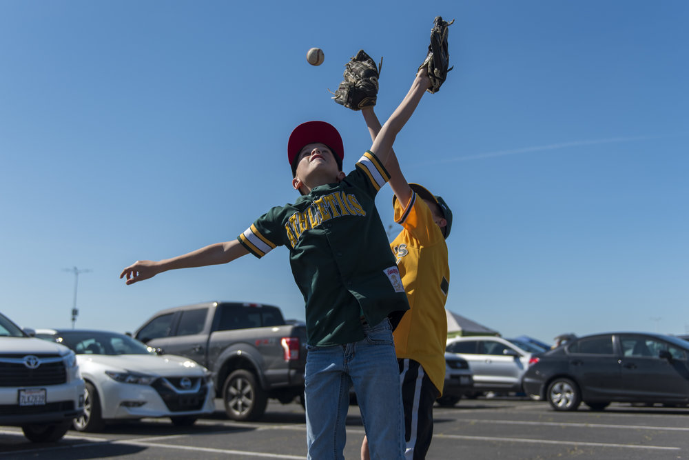 Chase (left) and Dash Dutcher play in the Oakland Coliseum parking lot before the A's play the L.A. Angels on Thursday, March 29, 2018. | Rosa Furneaux, Special To The Chronicle