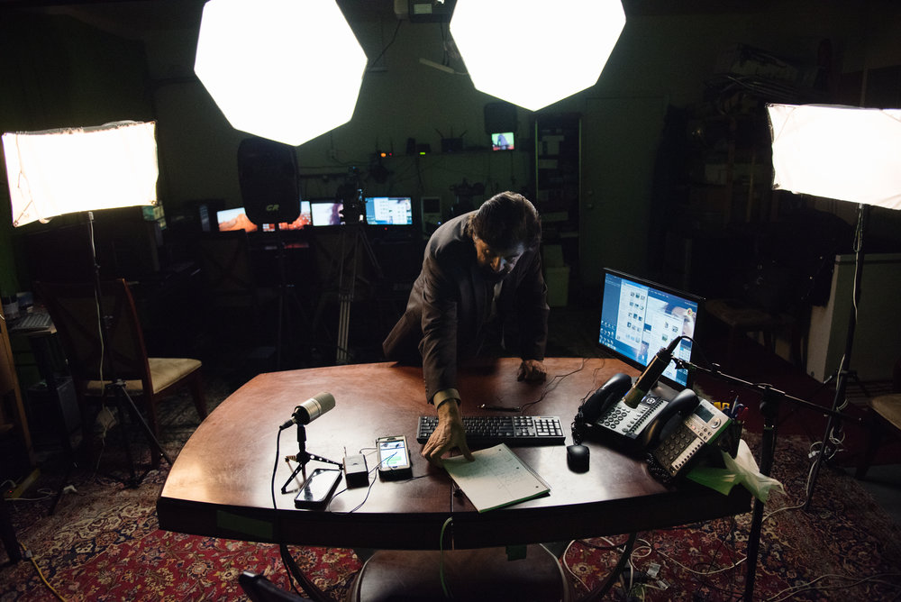 Haroon Ebrat rearranges his desk during an intermission in his Afghan variety show, filmed live in the garage of his family home in Pittsburg, California, on Sunday, February 11 2017. | Rosa Furneaux for Pacific Standard Magazine