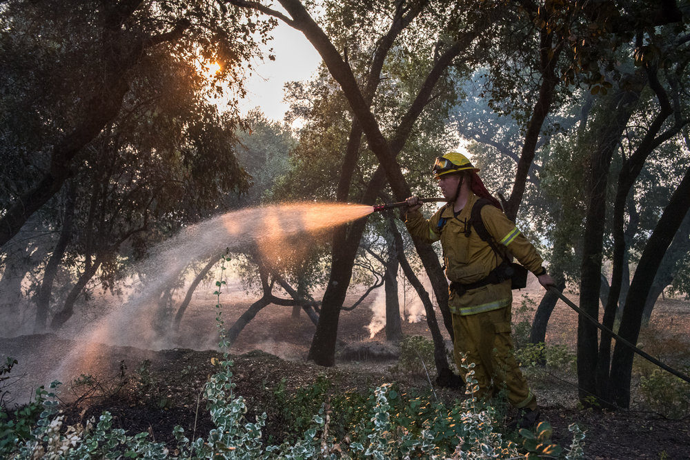 Firefighter Jake McClendon, of Rancho Adobe, works to protect a home on Castle Road just two miles from Sonoma town center, as the sun rises on Saturday, 14 October 2017.