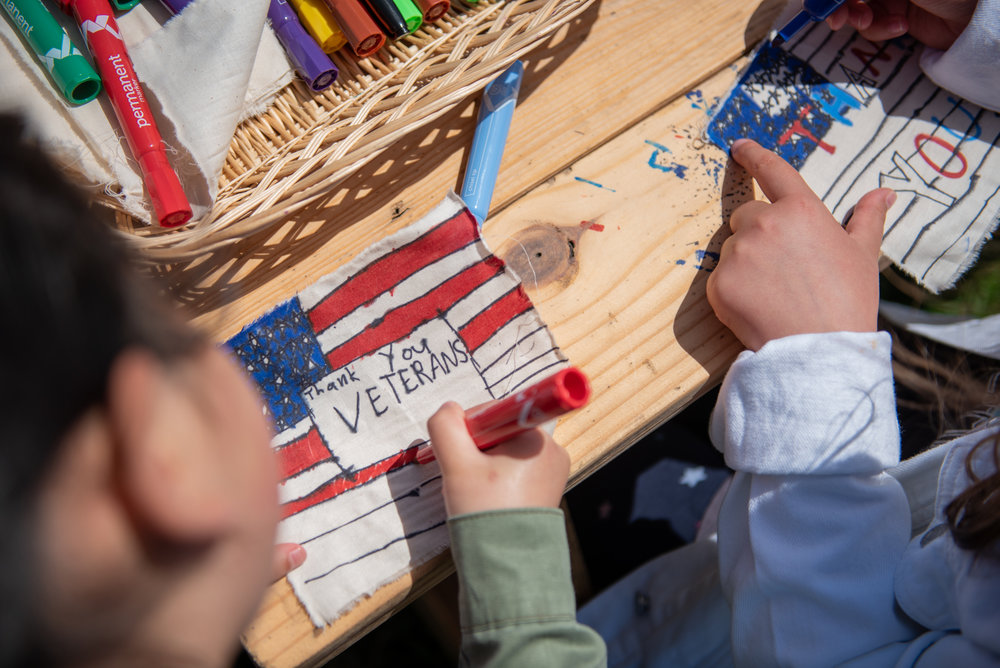 Addison Kim, 7, and Sophie Philhour, 8, decorate their flags for the Presidio Trust's Civilian Veteran Flag Collage on Sunday, May 27, 2018. | Rosa Furneaux, Special To The Chronicle