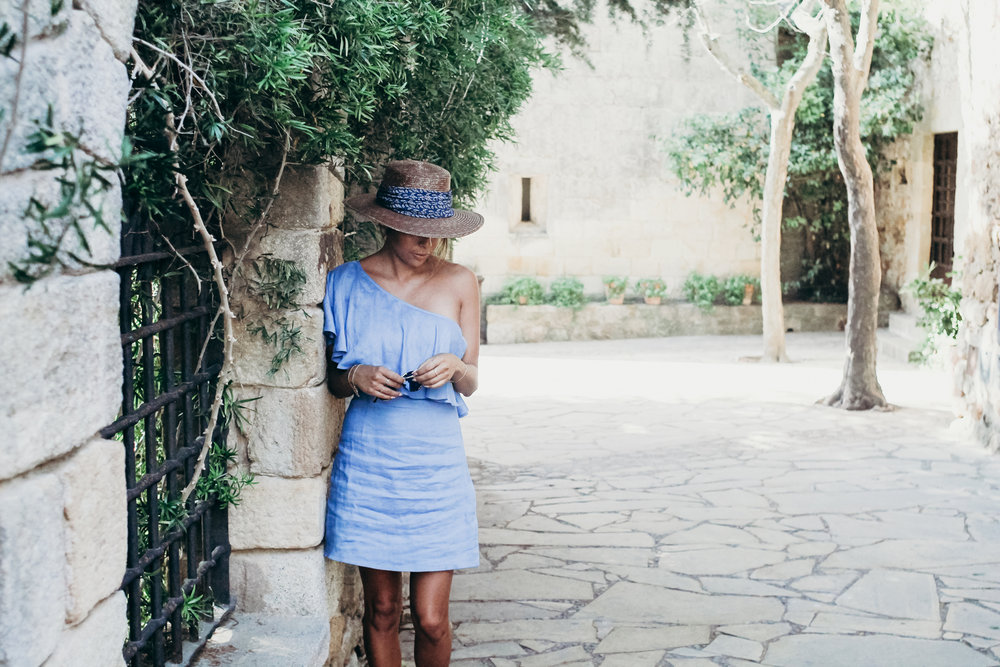 what to wear during the summer in Europe: linen dress, wide-brimmed hat, and sandals