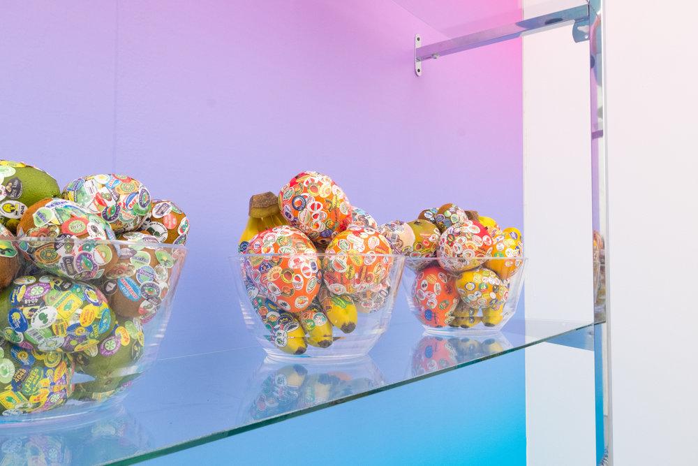 Adriana Martínez / Fruits, 2017 / Frutas plásticas y pegatinas con logos de multinacionales