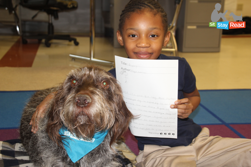 Certified Reading Assistance Dog Jack and second-grade student Hope.png