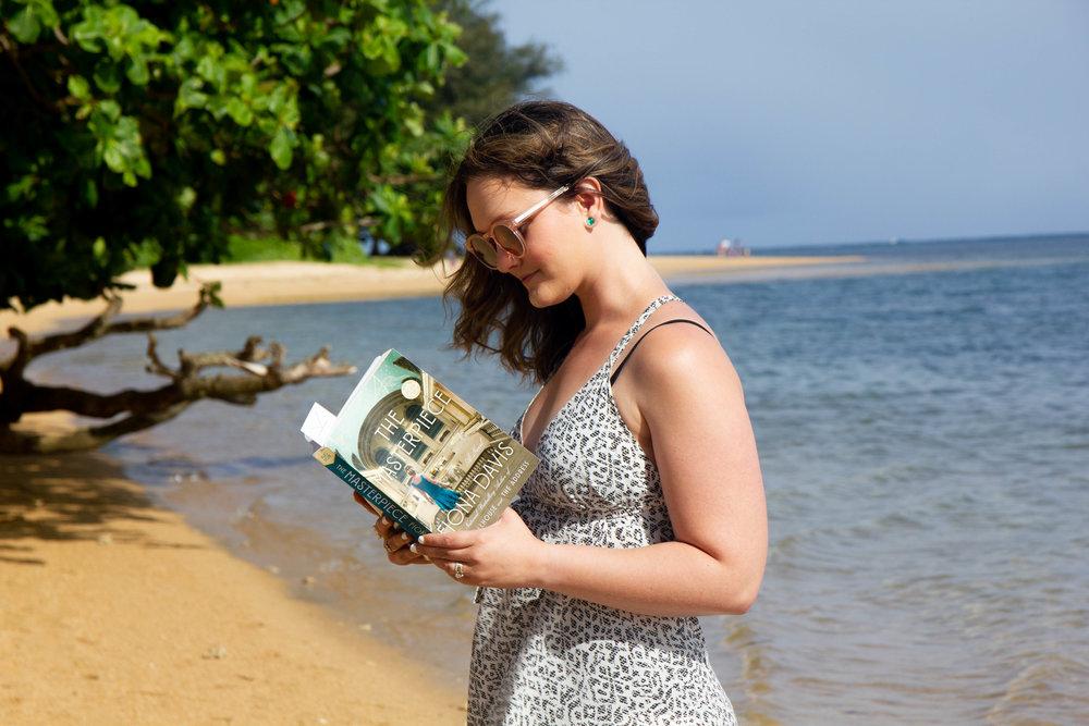 Reading The Masterpiece on Anini Beach in Kauai, Hawaii