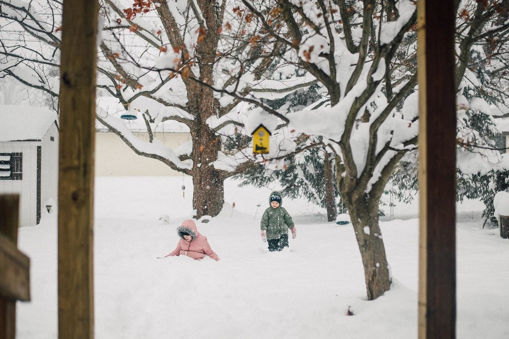 sister-playing-in-snow-filled-yard-during-snowfall-by-erie-pennsylvania-family-photographer-anna-margaret-photography.jpg
