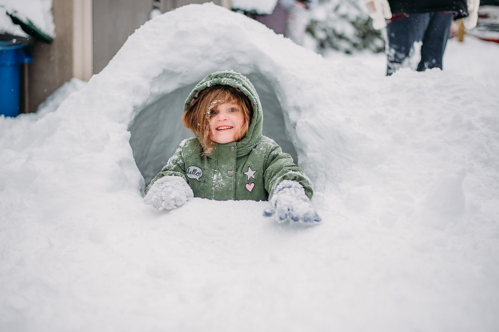 preschool-girl-in-green-jacket-playing-in-snow-fort-by-erie-pennsylvania-family-photographer-anna-margaret-photography.jpg