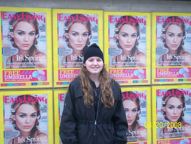 A young Mrs. Nerd standing in front of some Keira Knightly posters in London