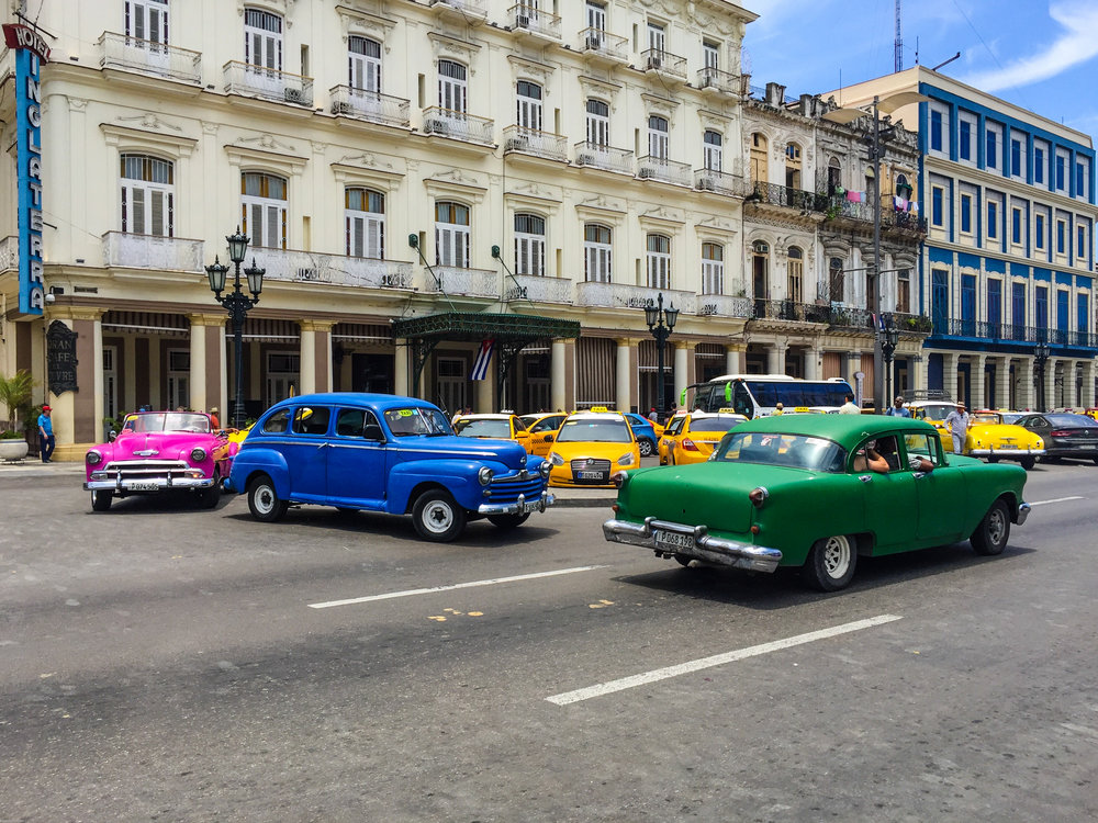 Multiple old cars and yellow taxis