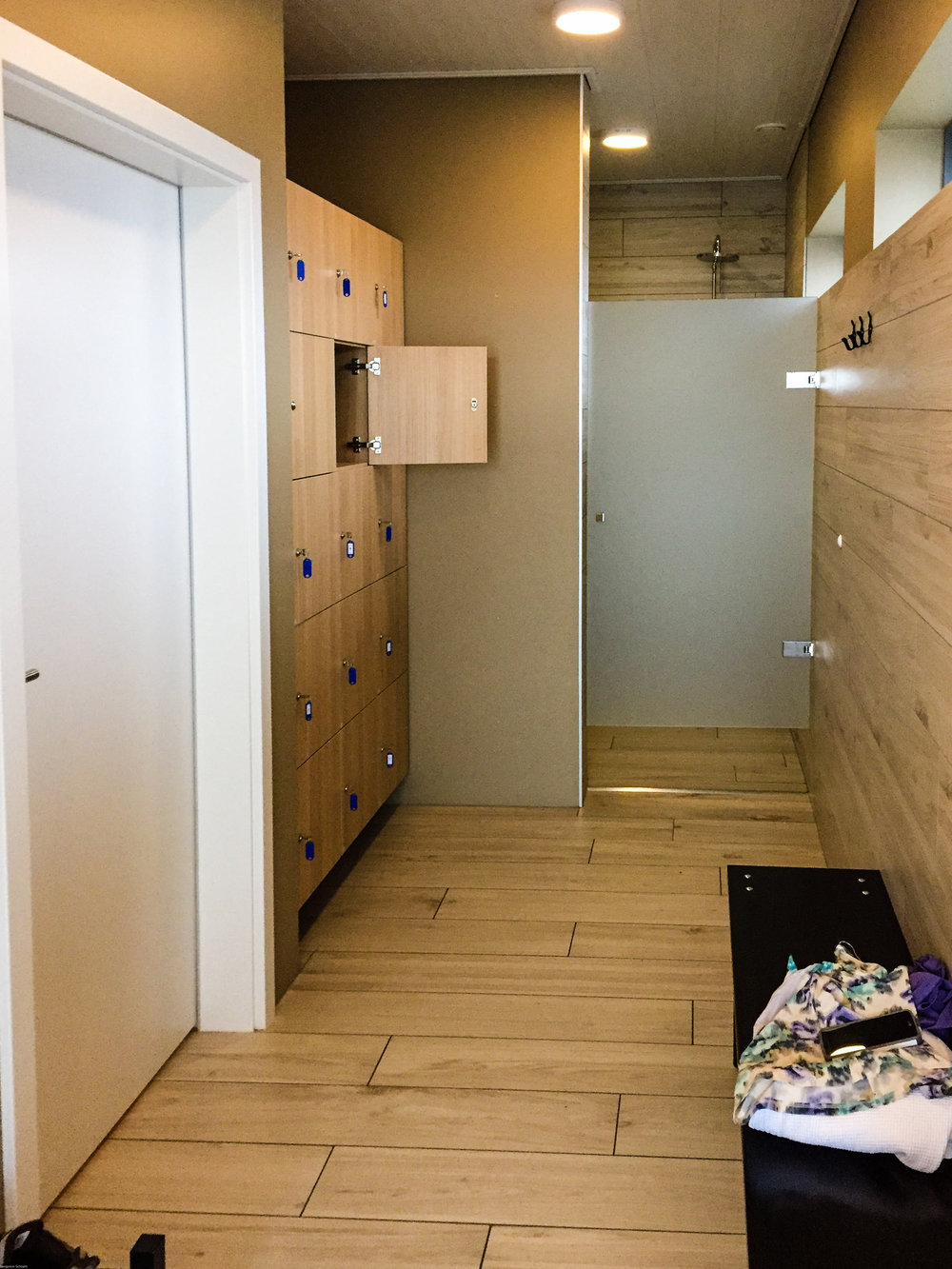 The dressing room with bathroom, cubbies, and shower