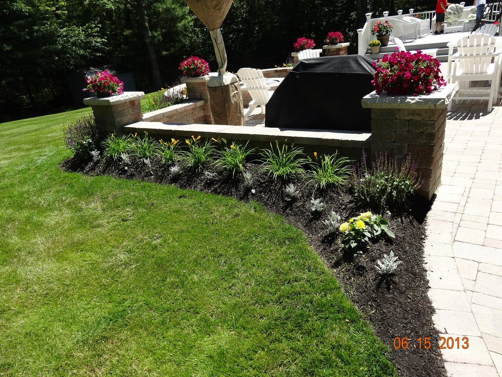Front yard landscaping with stunning retaining wall in Millis