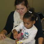 AmeriCorps VISTA, Alyssa Mitchell, leads a child in an EMERGE enrichment activity.