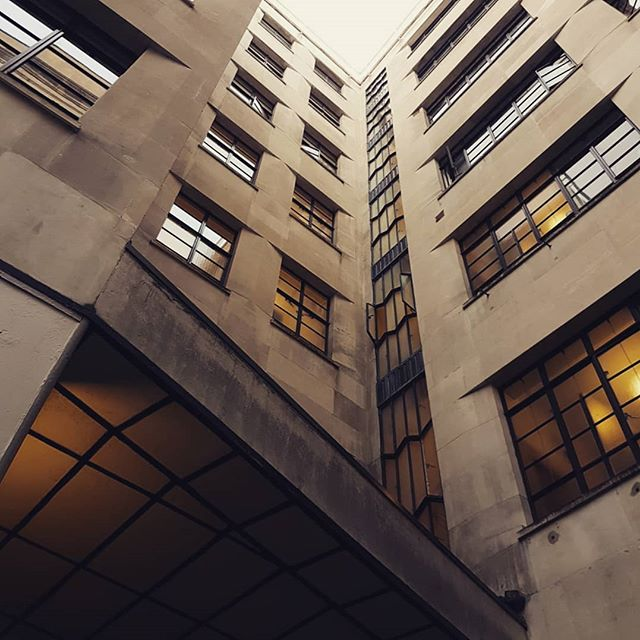 St Olaf House opposite London Bridge underground. Tasteful art deco modernism on the facade with beautiful chamfered brass signage and faceted angles in the window framing, patterns which are unleashed in a wildly unexpected and almost pop art undercroft.  #artdeco #stolafhouse #architecture #instaarchitecture #modernistarchitecture #ceiling #brassletters #portlandstone