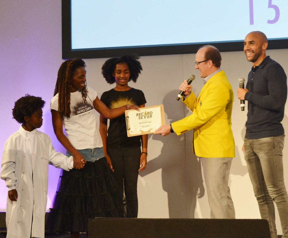 Michelle De Leon, founder of World Afro Day receiving the Record Setters World Record for largest hair education lesson