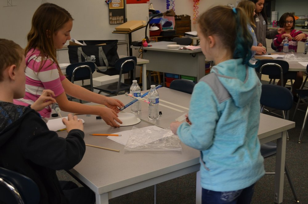 Students use everyday household materials, such as water bottles and rulers, to create trebuchets.