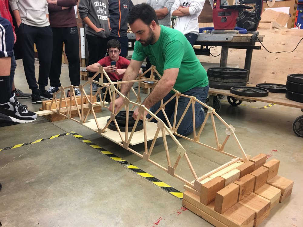 MTHS STEM teacher, Bryan Smelcer, tests a bridge.