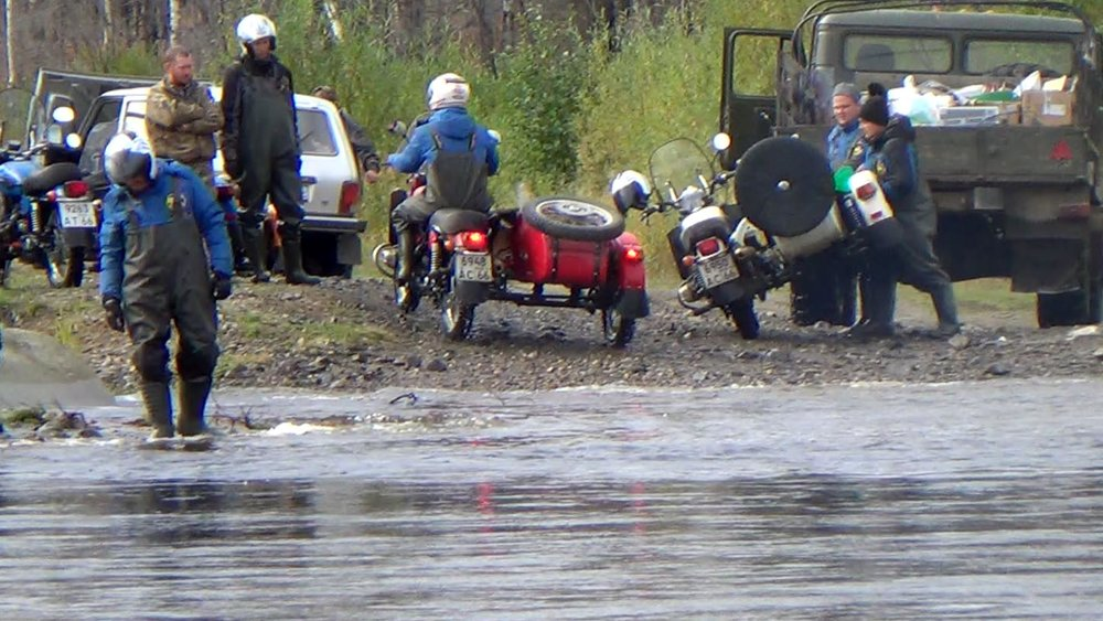 After a deep water crossing, the guys bail water out of the tub of the white Ural.
