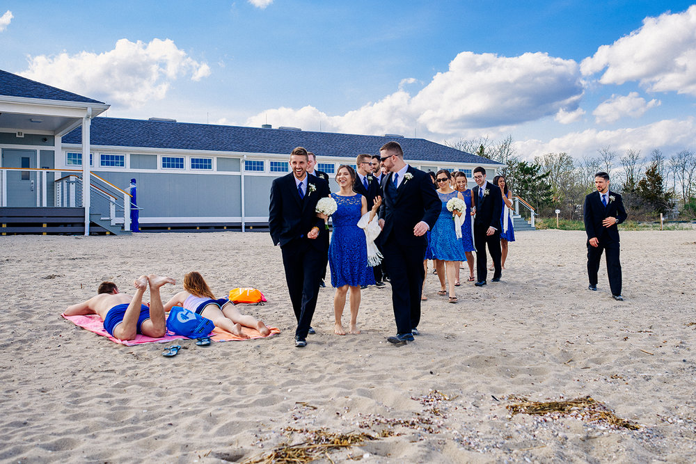 Wedding party photos at Fairfield Beach in Fairfield, CT. Bride and groom at the beach, bridal New England beach portraits, and wedding party fun photos at the beach.