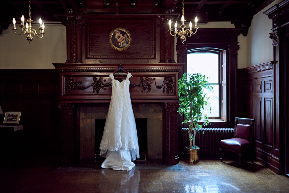 Wedding dress hanging by fancy fireplace