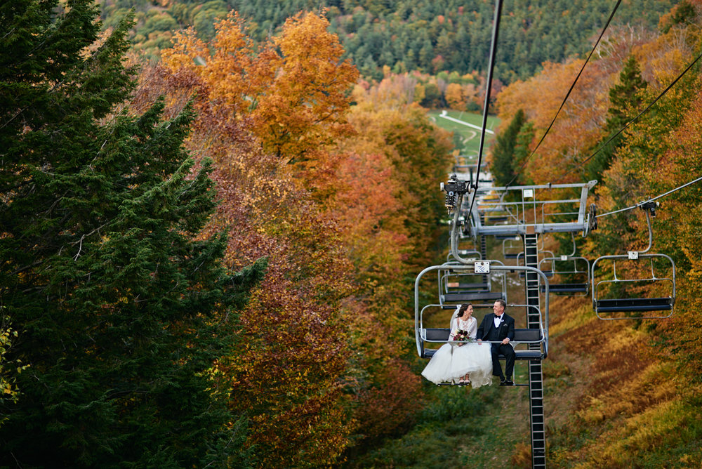 Wedding Photography by Cate Bligh, the bride rides the chairlift at Mount Sunapee Resort in Newbury, NH with her father
