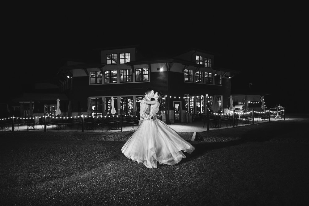 A 'Goodnight' photo with the beautiful bride with her now husband kissing in front of the Sunapee Lodge lit up at night.