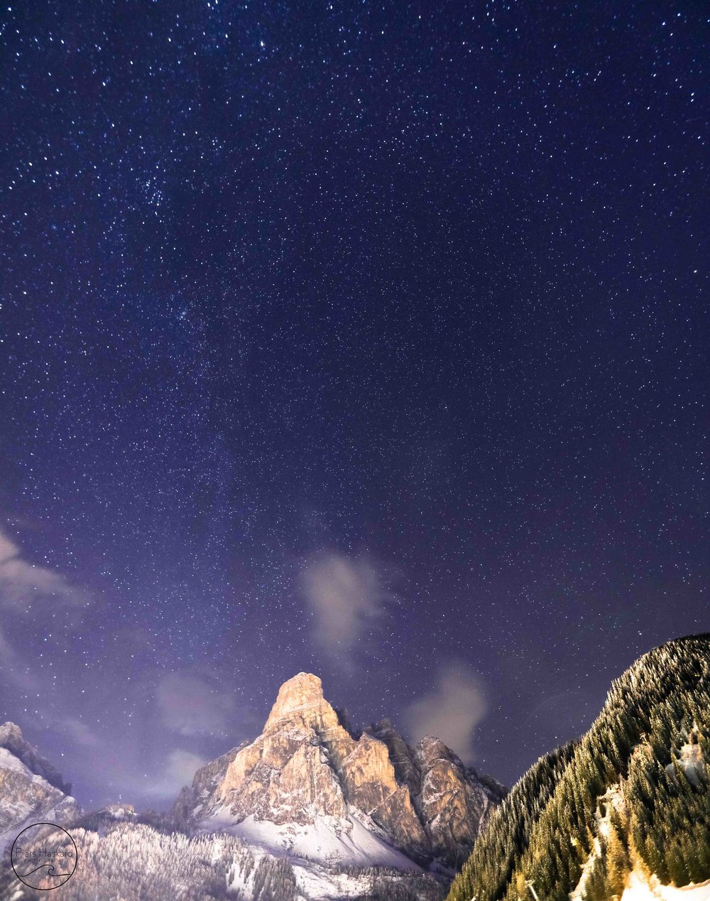 Sassongher Mountain looming above Corvara village on a clear night.