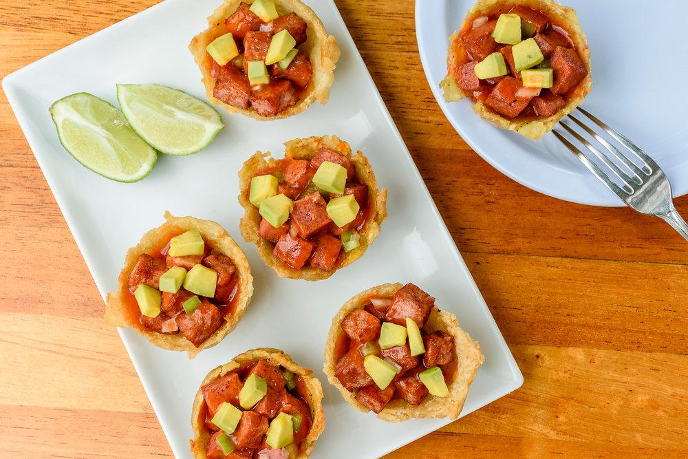 Las Canasticas Criollas están compuestas de tres de yuca con salami guisado y tres de guineito con jamón york guisado. Contienen también trocitos de aguacate.
