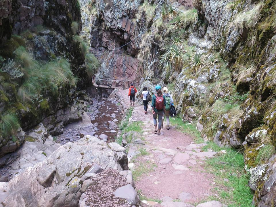 Group trekking through scenic gorge above Huchuy Qosqo ruins.jpg